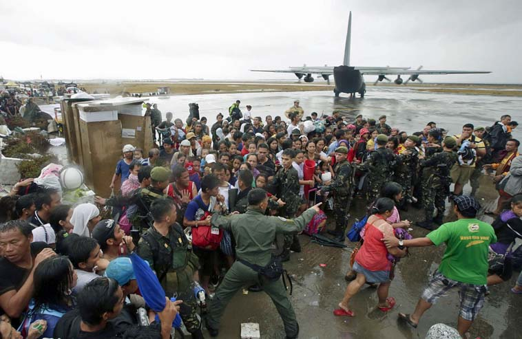 Image: Typhoon survivors rush to get a chance to board a C-130 military transport plane in Tacloban city